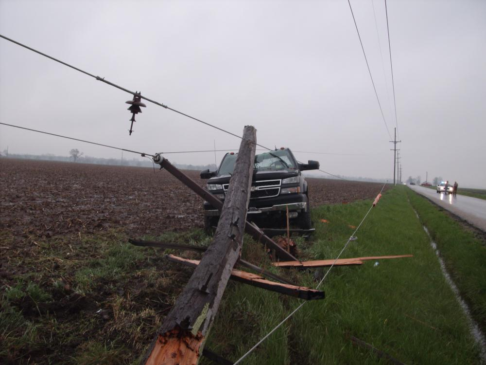 Image of vehicle accident involving breaking a pole, pulling lines down